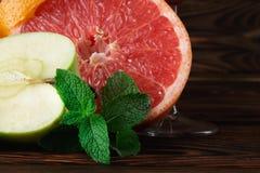 Крупный план свежих зеленых листьев мяты, сочного яркого грейпфрута и яблока на деревянной коричневой предпосылке Стоковое Фото