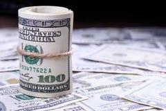 Крупный план свернутых американских банкнот доллара на левой стороне 5000 рублевок картины дег счетов предпосылки Стоковое Изображение
