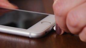 Крупный план смартфона поручая с поручая шнуром Введите поручая шнур в соединитель смартфона видеоматериал