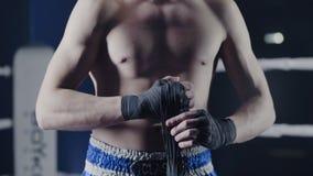 Крупный план смешанного бойца боевых искусств оборачивая его руки перед боем Боксер оборачивает его руку красная повязка перед Стоковое Фото