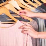 Крупный план снял рук женщины которые выбирающ новые одежды Стоковое фото RF