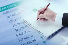 Крупный план сочинительства руки бизнесмена на бумаге на столе Стоковое Фото