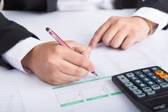 Крупный план сочинительства руки бизнесмена на бумаге на столе Стоковое фото RF