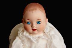 Крупный план старой куклы фарфора с голубыми глазами на черной предпосылке Стоковые Фотографии RF