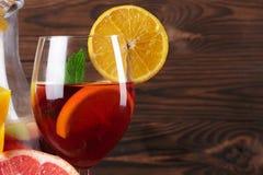 Крупный план стекла напитка с клубниками и частями яблока и разрешения мяты на деревянной предпосылке Стоковые Фото