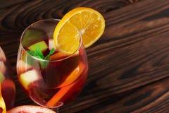 Крупный план стекла напитка с клубниками и частями яблока и разрешения мяты на деревянной предпосылке Стоковые Изображения