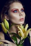 Крупный план стороны девушки красоты искусства с лилиями в руках на черном backg Стоковые Изображения RF