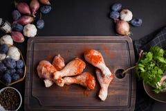 Крупный план сырцовых бедренных костей цыпленка с смесью чеснока, паприки, соли и перца на темной предпосылке Взгляд сверху Вокру Стоковые Изображения RF