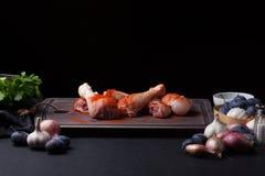 Крупный план сырцовых бедренных костей цыпленка с смесью чеснока, паприки, соли и перца на темной предпосылке Вокруг вырезывания Стоковые Фото