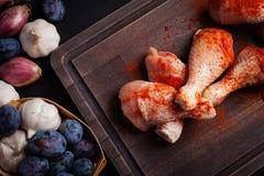 Крупный план сырцовых бедренных костей цыпленка с смесью чеснока, паприки, соли и перца на темной предпосылке Взгляд сверху Вокру Стоковое Фото