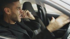 Крупный план телефона бизнесмена Stressed присягая и говоря пока сидящ внутри автомобиля outdoors Стоковые Изображения