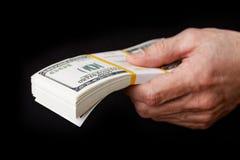 Крупный план a укомплектовывает личным составом руку держа пакет банкнот долларов Стоковые Фото