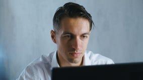 Крупный план управляющего корпорации молодого человека работая в офисе используя компьютер Кофе или чай бизнесмена выпивая и сток-видео