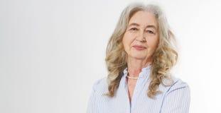Крупный план усмехаясь старшей стороны морщинки женщины и серых волос Старая зрелая дама касаясь ее сморщенной коже изолированной стоковое изображение rf