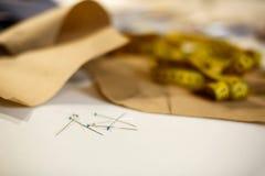 Крупный план установил на иглы, сантиметр и картину бумаги на рабочем столе портноя Концепция индустрии портноя стоковые изображения