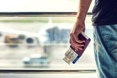 Крупный план человека держа пасспорты и посадочный талон на авиапорте T стоковое изображение