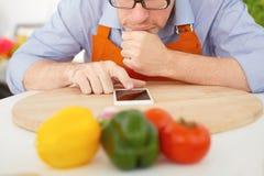 Крупный план человека указывая палец к smartphone n предпосылка кухни Стоковая Фотография