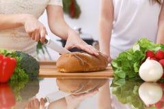 Крупный план человеческих рук варя в кухне Мать и дочь или 2 женских друз режа хлеб здоровая еда Стоковая Фотография