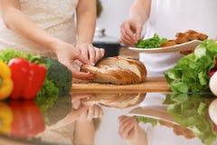 Крупный план человеческих рук варя в кухне Мать и дочь или 2 женских друз режа хлеб здоровая еда Стоковое фото RF