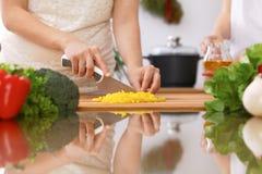 Крупный план человеческих рук варя в кухне Мать и дочь или 2 женских друз режа овощи для свежего салата Стоковое Фото
