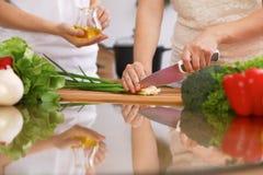 Крупный план человеческих рук варя в кухне Мать и дочь или 2 женских друз режа овощи для свежего салата Стоковые Изображения RF