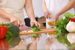 Крупный план человеческих рук варя в кухне Мать и дочь или 2 женских друз режа овощи для свежего салата Стоковая Фотография