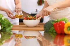 Крупный план человеческих рук варя в кухне Мать и дочь или 2 женских друз режа овощи для свежего салата Стоковое Изображение RF