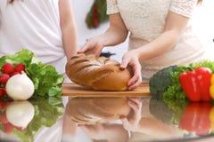 Крупный план человеческих рук варя в кухне Мать и дочь или 2 женских друз режа хлеб здоровая еда Стоковое Фото