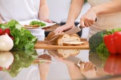 Крупный план человеческих рук варя в кухне Мать и дочь или 2 женских друз режа хлеб здоровая еда Стоковые Фото