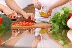 Крупный план человеческих рук варя в кухне Мать и дочь или 2 женских друз режа овощи для свежего салата Стоковые Фотографии RF