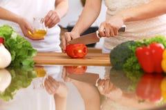 Крупный план человеческих рук варя в кухне Мать и дочь или 2 женских друз режа овощи для свежего салата Стоковые Фото