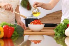 Крупный план человеческих рук варя в кухне Мать и дочь или 2 женских друз режа овощи для свежего салата Стоковые Изображения
