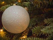 Крупный план шарика рождества с белым и серебром сверкнает стоковое фото