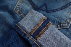 Крупный план шить в тумаке голубых джинсов джинсовой ткани стоковые изображения