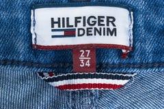 Крупный план ярлыка Tommy Hilfiger на голубых джинсах Tommy Hilfiger бренд образа жизни Джинсовая ткань Hilfiger Деталь голубых д Стоковая Фотография RF