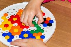 Крупный план child& x27; руки s принимая яркие части мозаики учащ цвета дома Стоковые Фото