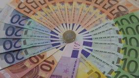 крупный план 4K монетки одно евро с банкнотами различных значений Деньги наличных денег видеоматериал