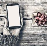 Крупный план smartphone в руках женщины и подарочной коробки с красным смычком на деревянном столе Стоковое Фото