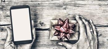 Крупный план smartphone в руках женщины и подарочной коробки с красным смычком на деревянном столе Стоковое Изображение