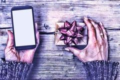 Крупный план smartphone в руках женщины и подарочной коробки с красным смычком на деревянном столе Стоковая Фотография RF