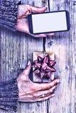 Крупный план smartphone в руках женщины и подарочной коробки с красным смычком на деревянном столе Стоковые Фото