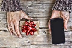 Крупный план smartphone в руках женщины и подарочной коробки с красным смычком на деревянном столе Открытый космос для текста Взг Стоковые Фото