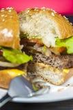 Крупный план аппетитного гамбургера с овощами на белой плите с вилкой на деревянном столе Стоковое Изображение RF