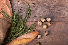 Крупный план багета пшеницы, хворостин душистого розмаринового масла, запятнанных яичек триперсток, приправ на светлой деревянной Стоковое Фото