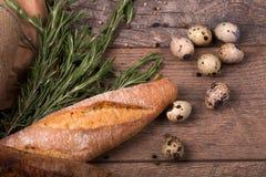 Крупный план багета пшеницы, хворостин душистого розмаринового масла, запятнанных яичек триперсток, приправ на светлой деревянной Стоковое Изображение