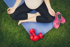 Крупный план беременной женщины размышляя на циновке фитнеса на парке Стоковые Фотографии RF