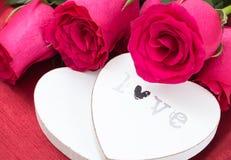 Крупный план 2 белых деревянных сердец и букетов роз, на красной ткани Стоковые Фото