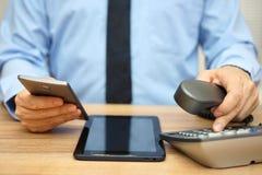 Крупный план бизнесмена вызывая клиентов и используя планшет Стоковые Фото