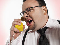 Крупный план бизнесмена выкрикивая в телефон Стоковая Фотография