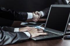 Крупный план бизнесмена работая на компьтер-книжке на предпосылке handshaking деловых партнеров Стоковая Фотография
